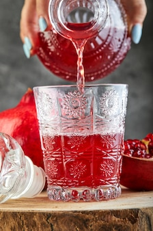 A female hand pours pomegranate wine into a glass.