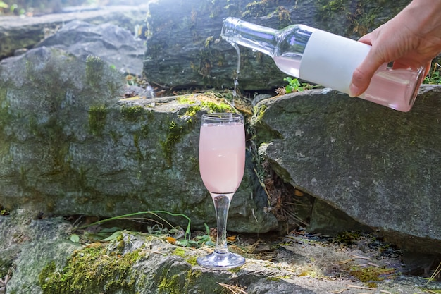 Женская рука наливает розовое вино из бутылки в рюмку на скале.