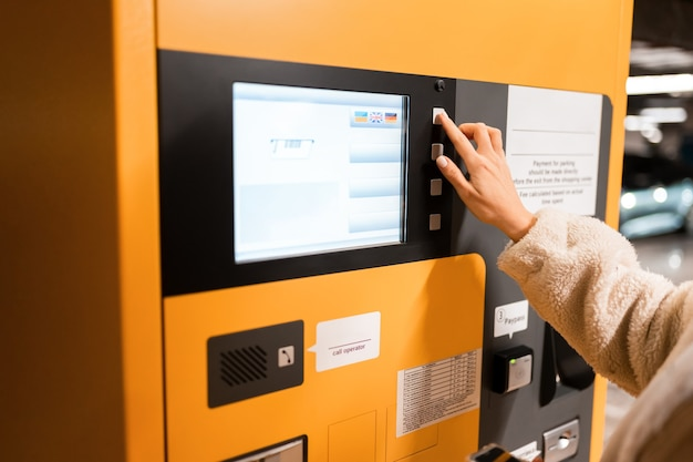 女性の手が駐車決済端末のボタンを押します。