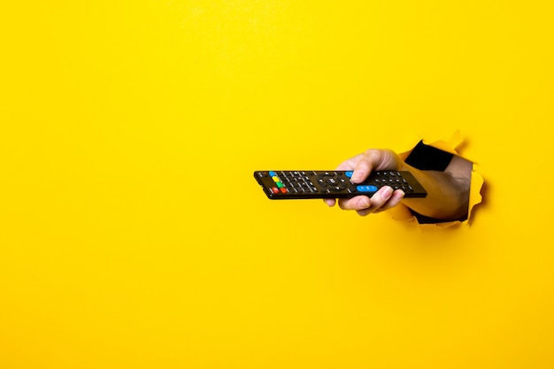 Женская рука нажимает кнопку на пульте дистанционного управления телевизора на ярко-желтом фоне