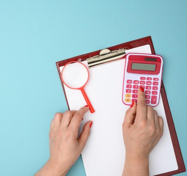 女性の手は、青い背景にプラスチックのピンクの電卓のキーを押します。財務分析、上面図