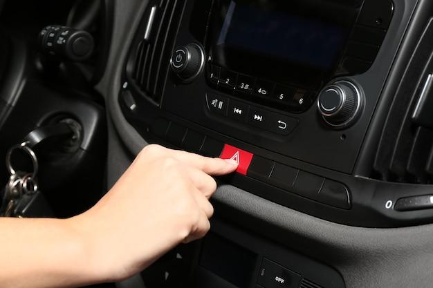 車のコンソールの緊急警告ボタンを押す女性の手