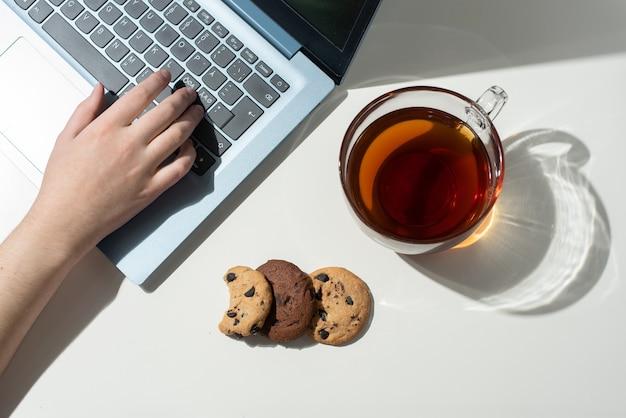여성의 손은 노트북, 차 한잔, 햇빛, 상위 뷰에서 세 개의 초콜릿 칩 쿠키에 인쇄됩니다.