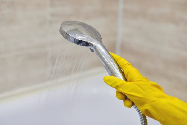 Female hand in protective yellow rubber glove holding shower head with pouring water in domestic bathroom, copy space, motion blur