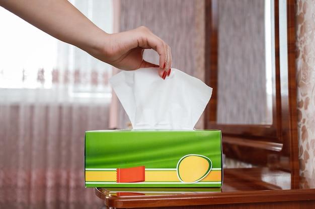 Женская рука вытаскивает салфетку из коробки