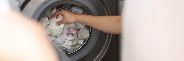 Женская рука вытаскивает чистое белье из стиральной машины крупным планом