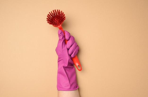 Female hand in purple rubber gloves holds a plastic cleaning brush on a beige background, copy spce