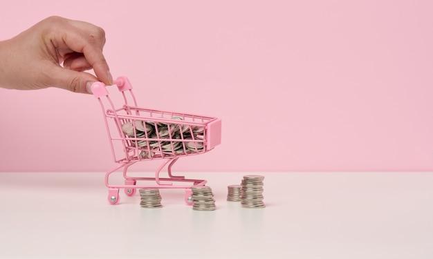 女性の手が白いテーブルにミニチュアの金属製のショッピングカートとコインのスタックを押します。割引と販売、予算の節約の概念。オンライン取引