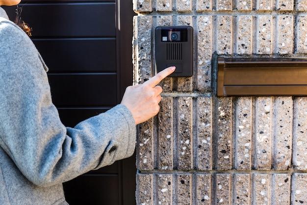 Female hand pushing the doorbell buzzer