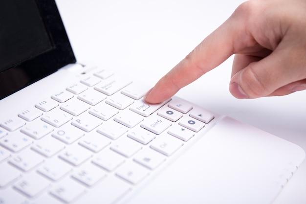 Женская рука, нажав кнопку ввода на белой клавиатуре ноутбука