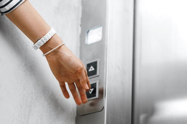 엘리베이터의 버튼을 누르면 여성 손 클로즈업