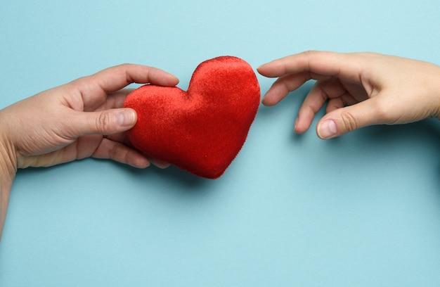 女性の手は、男性の手のひらに赤いハート、青い背景を置きます。優しさ、寄付、上面図の概念