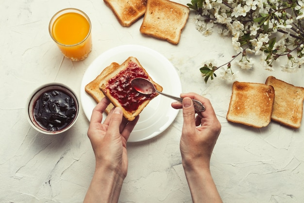 Female hand put jam on bread toast, glass of orange juice, sprigs spring tree with flowers, white stone surface. breakfast concept. flat lay, top view