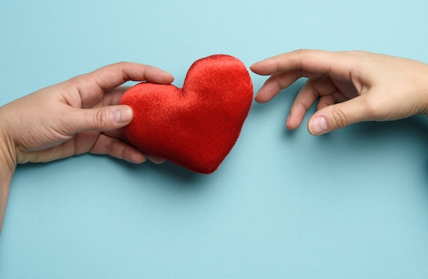 Female hand put a red heart in men's palms, blue background. concept of kindness, donation, top view