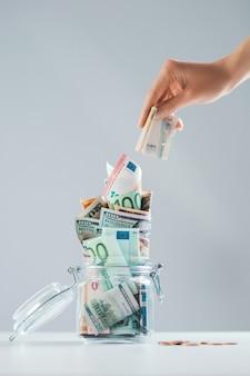 여성 손 돈이 가득한 유리 저금통에 지폐를 넣습니다.