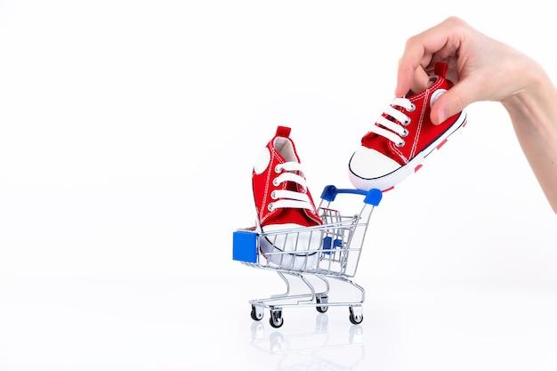 Женская рука кладет детские красные кроссовки в корзину, изолированную на белом фоне. интернет-магазин детской обуви. скопируйте пространство.