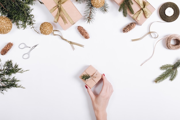 Female hand puts a box with a gift on the table with christmas balls, fir branch, ribbon, rope and scissors
