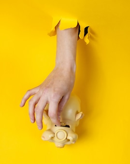 Female hand puts coin into the piggy bank through torn yellow paper hole. minimalistic creative concept