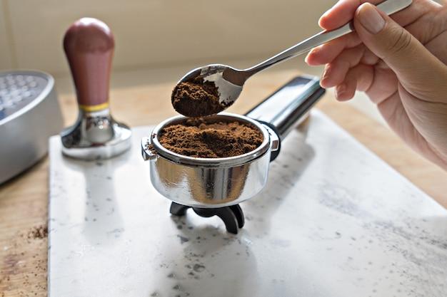 Female hand puts fresh ground coffee in portafilter