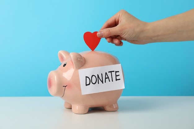 Female hand puts heart in piggy bank with text donate against blue space