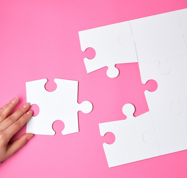 Female hand puts white big puzzles on pink