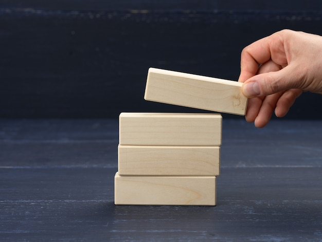 Женская рука кладет деревянные блоки друг на друга. концепция планирования целей, новые знания, стратегия и управление