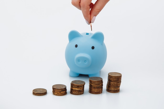 Female hand putting a coin into a blue piggy bank. money saving concept