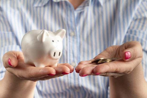 Female hand putting coin into piggy bank closeup