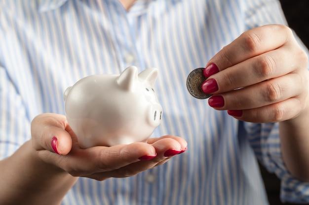 Женская рука положить монету в копилку крупным планом