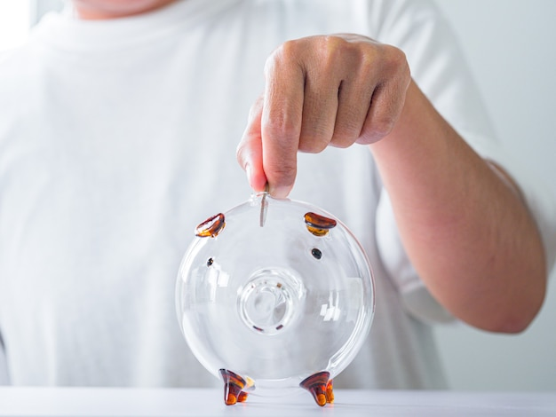 Female hand putting coin into piggy bank on white table closeup