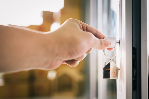 Female hand putting house key into front door lock of house.