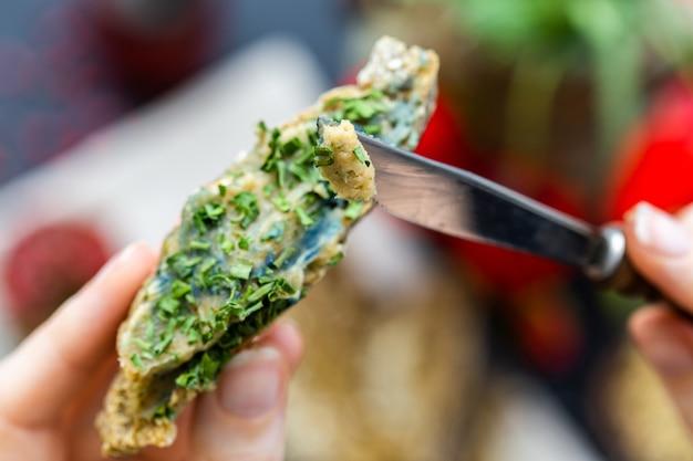 Mano femminile che mette la cipolla su un pane vegano crudo con un coltello