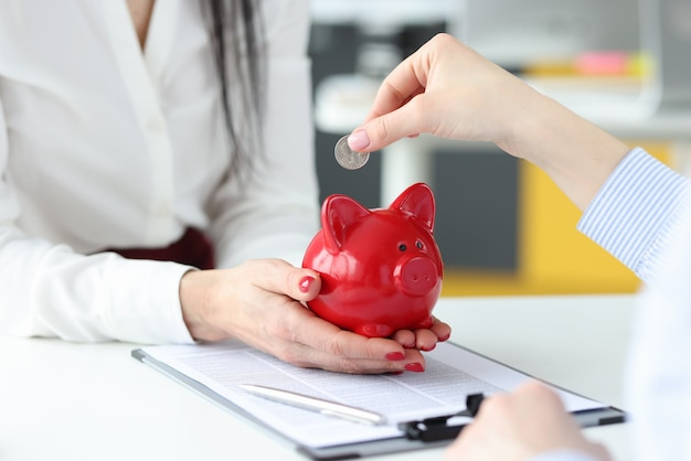 Female hand putting silver coin into red piggy bank closeup business investment concept