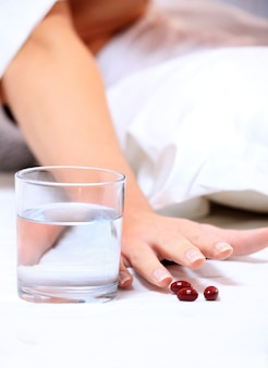 A female hand reaching for some tablets over white background