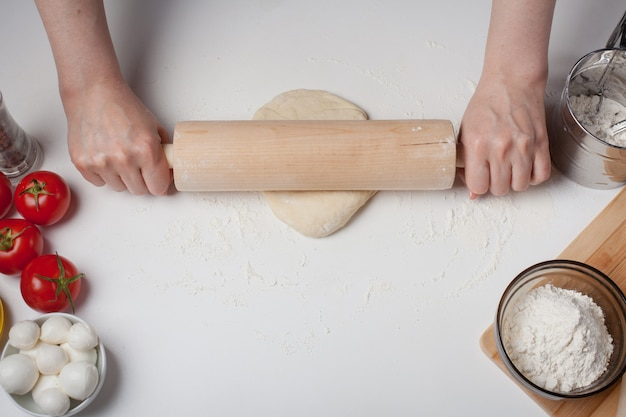 Female hand rolled pizza dough.