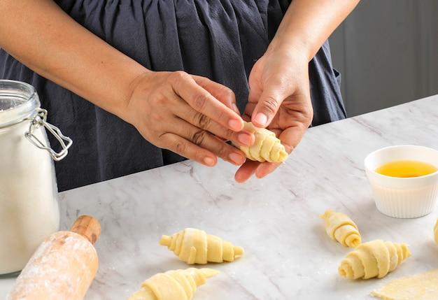 生地をロールパンに丸める女性の手、クロワッサンを作るベーキングプロセス。選択された焦点、ベーカリーのコンセプト