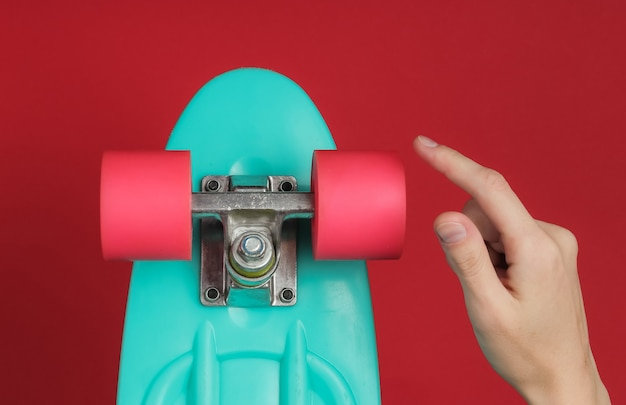 Female hand rotates the wheel of a cruiser board on a red paper