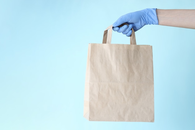 Female hand in rubber glove holding paper bag on blue background closeup