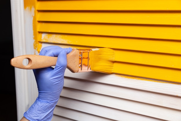Female hand in rubber glove with brush painting wooden door with yellow paint