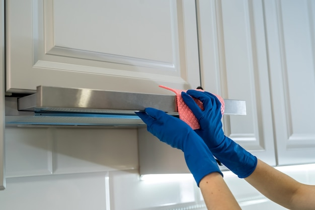 Female hand in rubber protective ã'âleaning cooker hood with rag in kitchen.