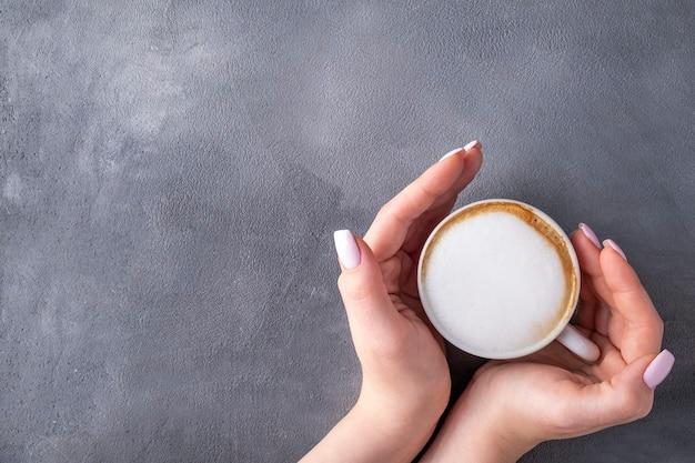 一杯のコーヒーを持っている女性の手。