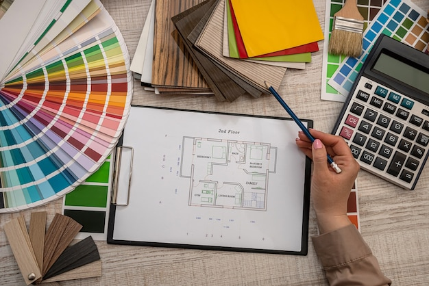 Female hand selects a color from the palette on architectural plan, renovation concept