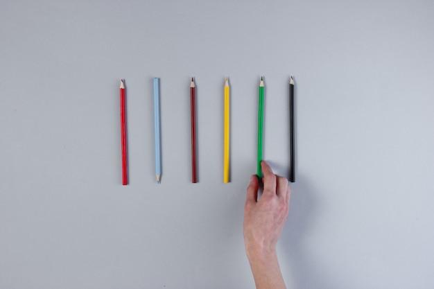 Женская рука выбирает цветной карандаш на серой поверхности