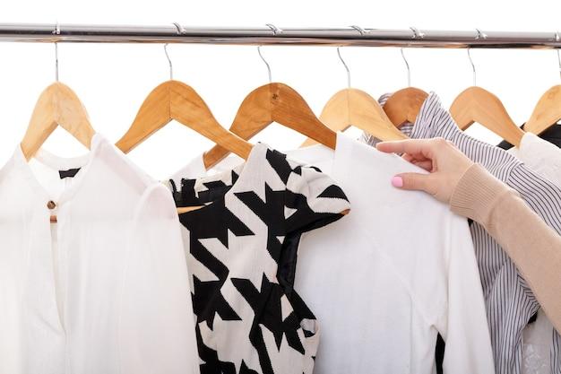 Женская рука выбирает новую модную одежду на деревянных вешалках на стойке на белом фоне, крупным планом. концепция покупок