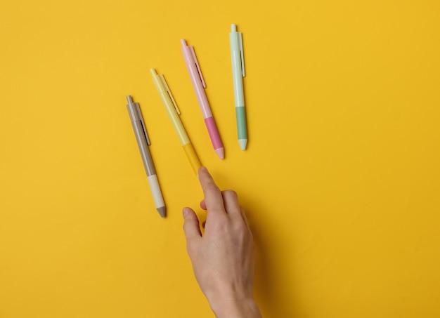 女性の手は黄色の背景にペンを選択します