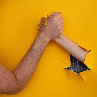 여성의 손은 찢어진 노란색 배경의 구멍에서 남성을 흔듭니다. 도움말 개념