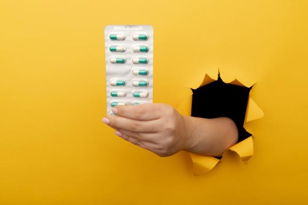 노란색 종이 벽에 찢어진 구멍에서 약의 물집을 보여주는 여성 손. 건강 관리, 조제 학 및 의학 광고.