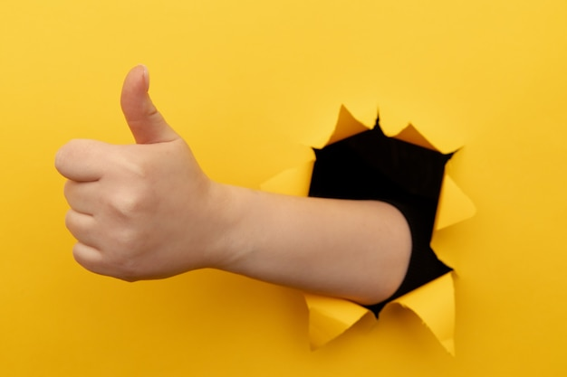 黄色い紙の壁の破れた穴から親指を立てるサインを示す女性の手。よくやった、良い仕事のコンセプト。