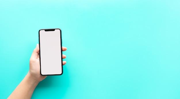 空白の画面を持つスマートフォンを示す女性の手