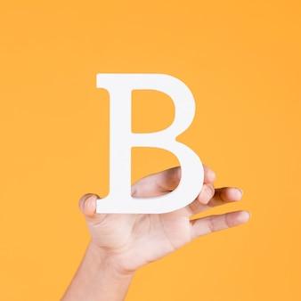 白い大文字bを示す女性の手